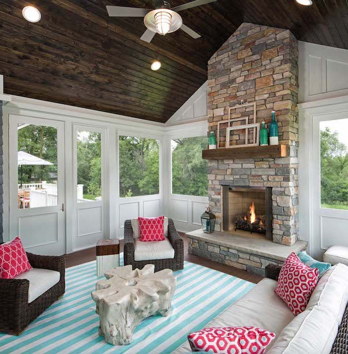 fireplace made of stone screened in deck wooden cathedral ceiling turquoise and white striped carpet red throw pillows