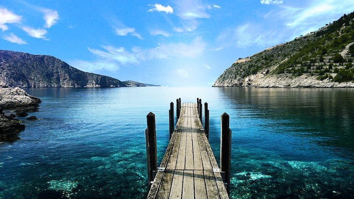 free wallpaper for computer wooden pier leading to a lake with turquoise water surrounded by hills