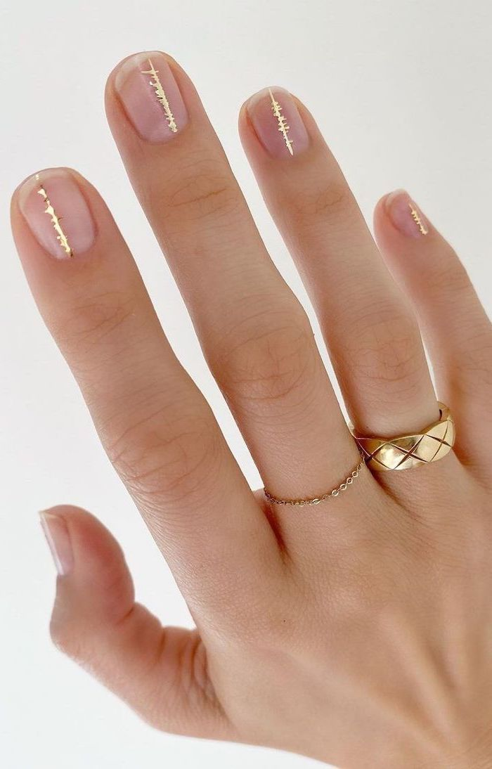 gold decorations on top of transperant nail polish on short squoval nails simple nail designs