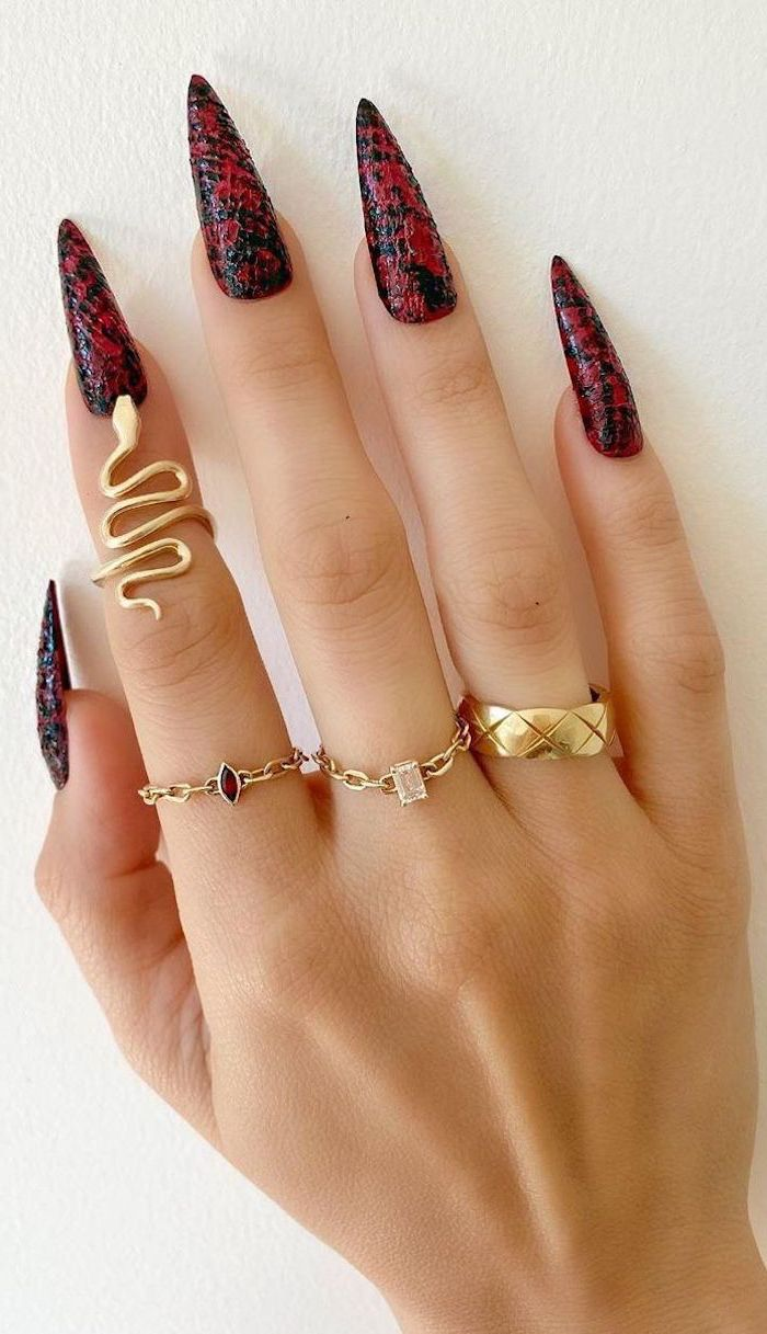 gold rings on fingers with long stiletto nails simple nail designs black and red snake skin print on the nails