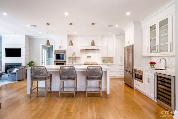 gray stools next to white kitchen island white farmhouse kitchen white cabinets white countertops wooden floor white tiles backsplash