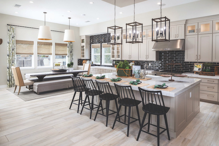 gray wooden kitchen island with marble countertop black stools farmhouse kitchen backsplash with black tiles white cabinets