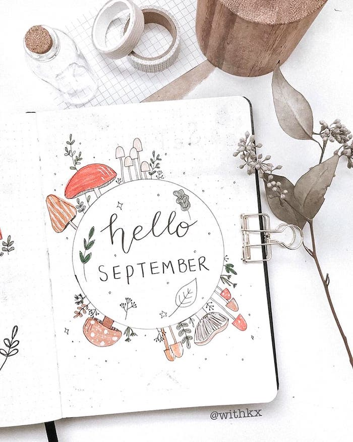hellow september page with drawings of fall mushrooms on white notebook bullet journal ideas for beginners washi tape next to the journal