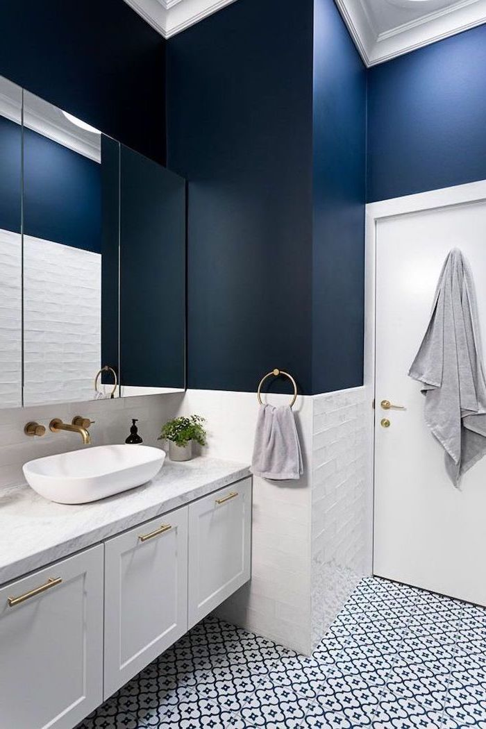 how to decorate a bathroom dark blue walls with white tiles at the bottom black and white patterned tiles on the floor floating white cabinet with marble countertop
