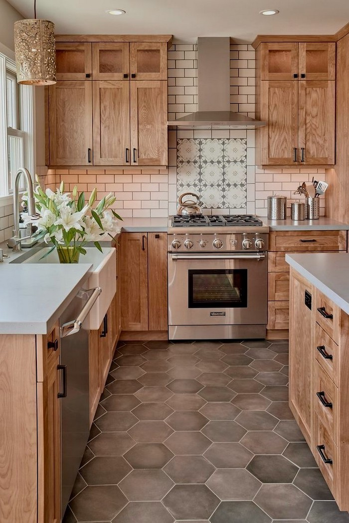 kitchen backsplash tile in white patterned tiles above the stove woooden cabinets and kitchen island with white countertops