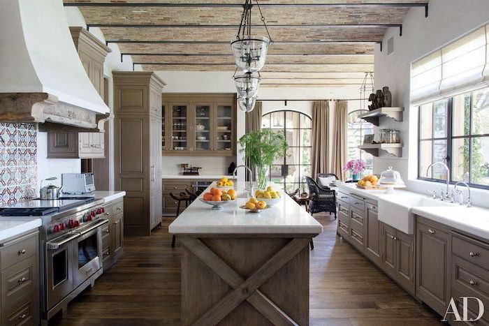 kitchen island with white countertop in the middle of kitchen modern farmhouse kitchen cabinets on both sides with white countertops dark wooden floor