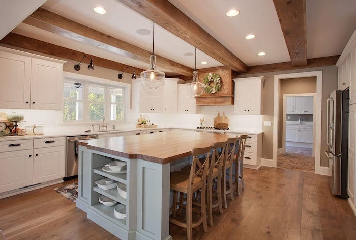 light gray kitchen island with wooden countertop wooden bar stools farmhouse kitchen decor ideas wooden floor exposed wood beams on the ceiling