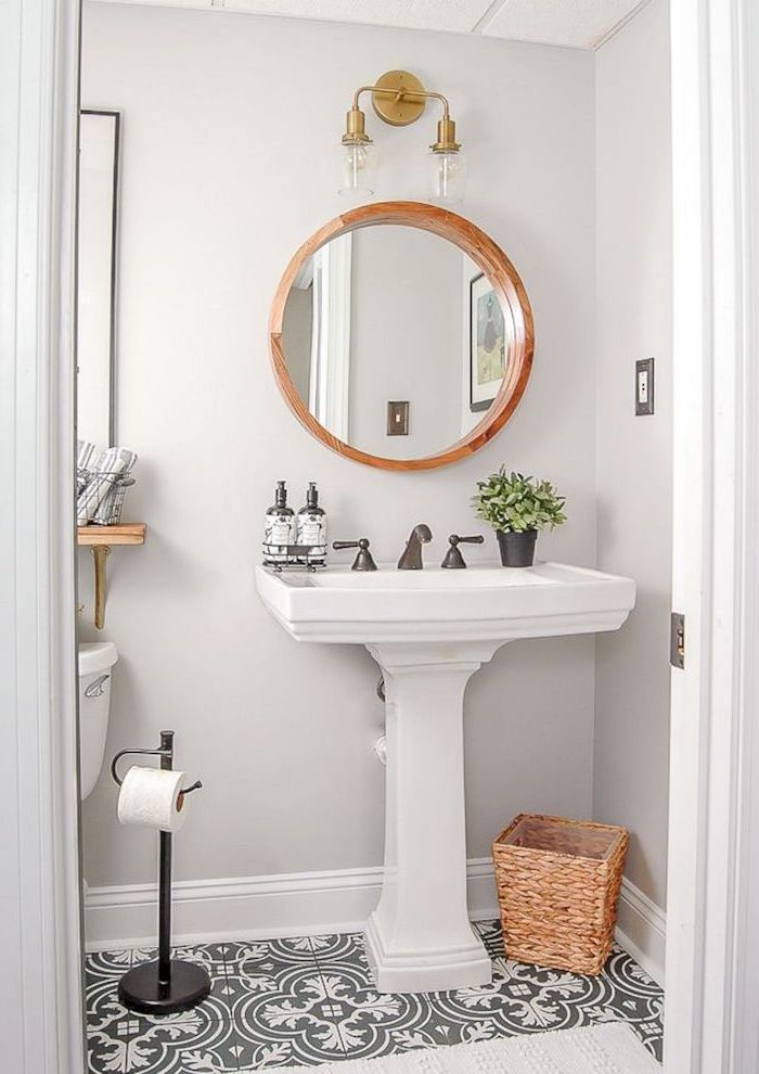 mirror with wooden frame above vintage sink black and white patterned tiles on the floor bathroom decor pictures white walls