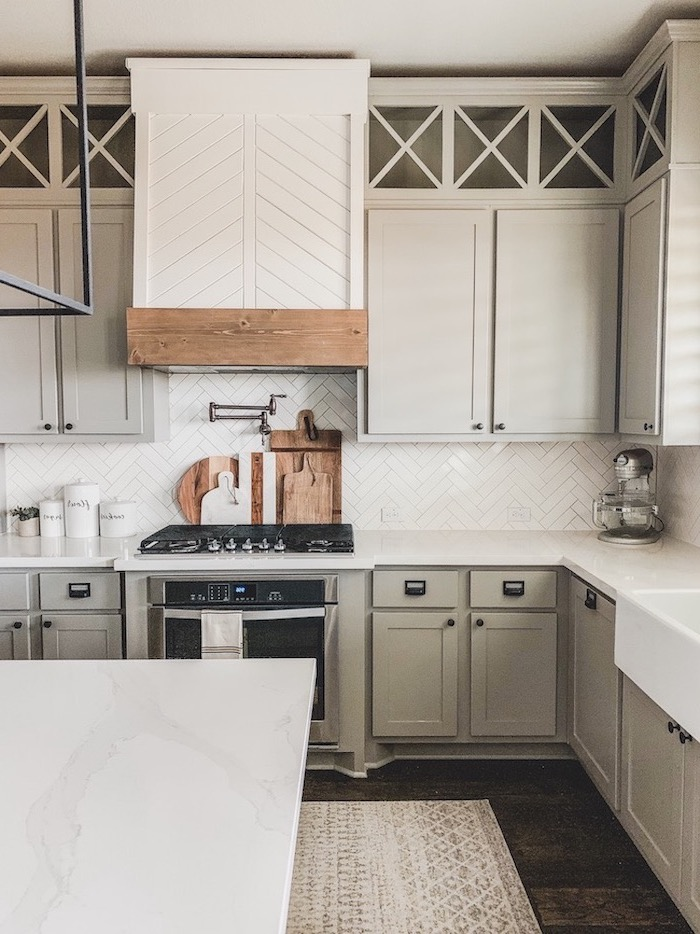 modern farmhouse kitchen light gray cabinets with white countertop and tiled backsplash dark wooden floor kitchen island