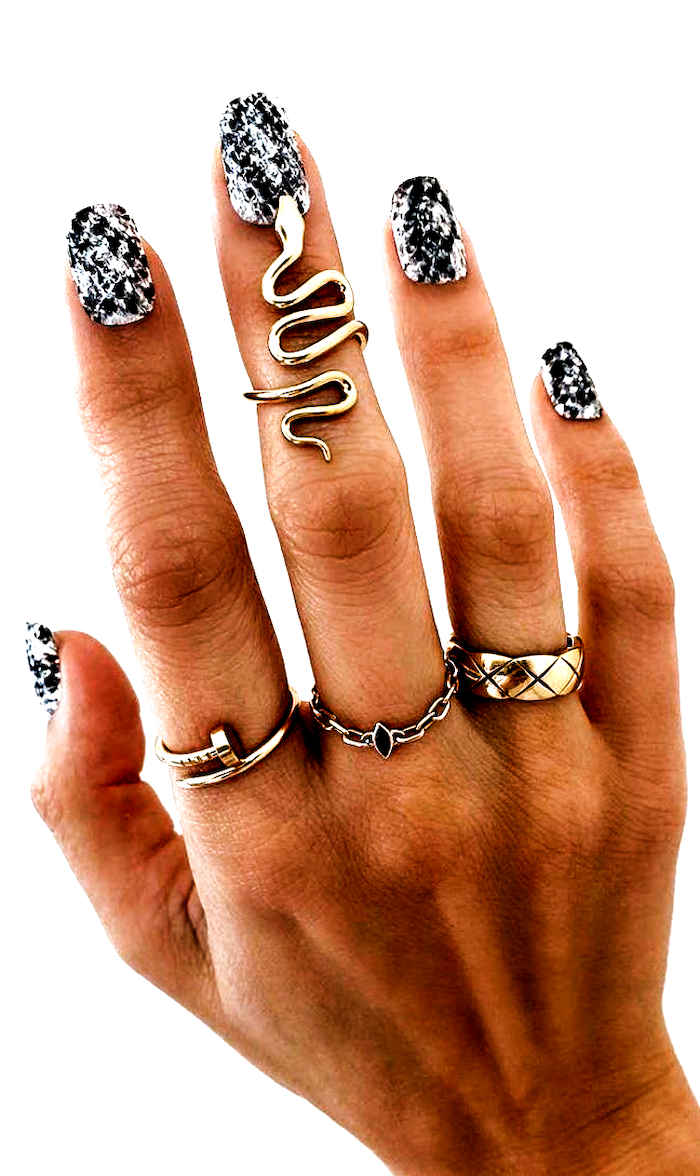 multi colored nails black and white snake skin print decorations on medium length almond nails gold rings on fingers