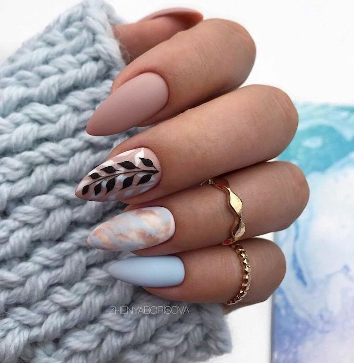 nude and blue matte nail polish simple nail designs blue and gold marble decoration on ring finger black leaves decoration on middle finger