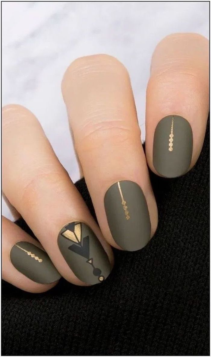olive green matte nail polish gold decorations on each finger multi colored nails short almond nails
