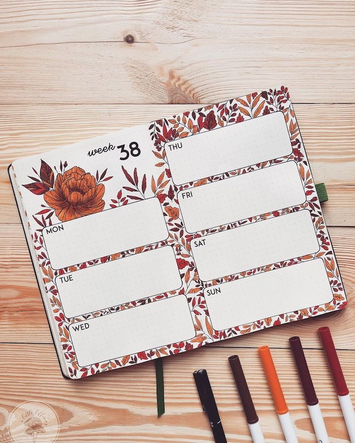 open notebook with weekly spread with orange flowers leaves drawn on it bullet journal weekly spread placed on wooden surface