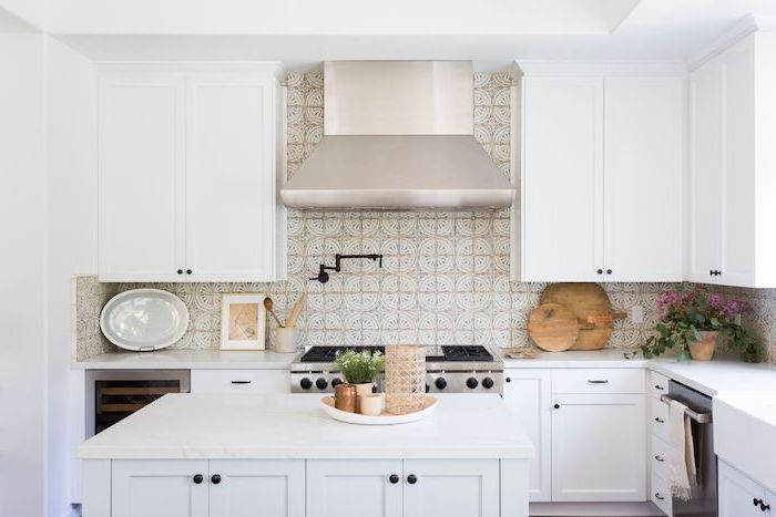 patterned tiles above the stove in white and beige subway tile backsplash white cabinets and kitchen island with white countertops