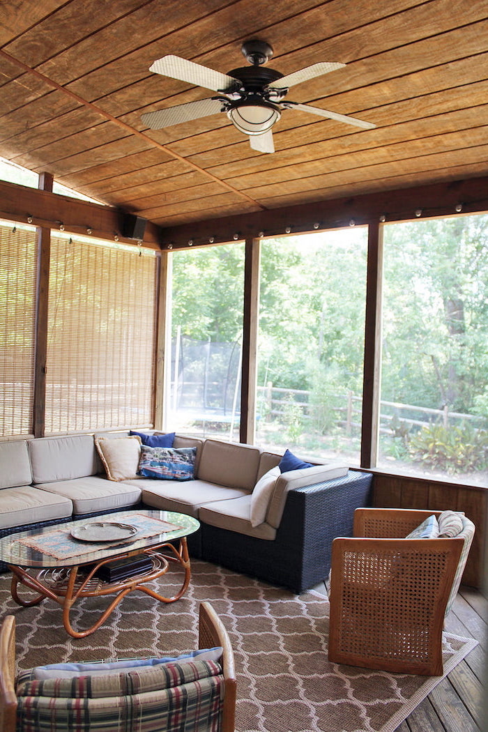 screened in patio wooden ceiling with fan garden furniture with white cushions blue throw pillows brown carpet on wooden floor