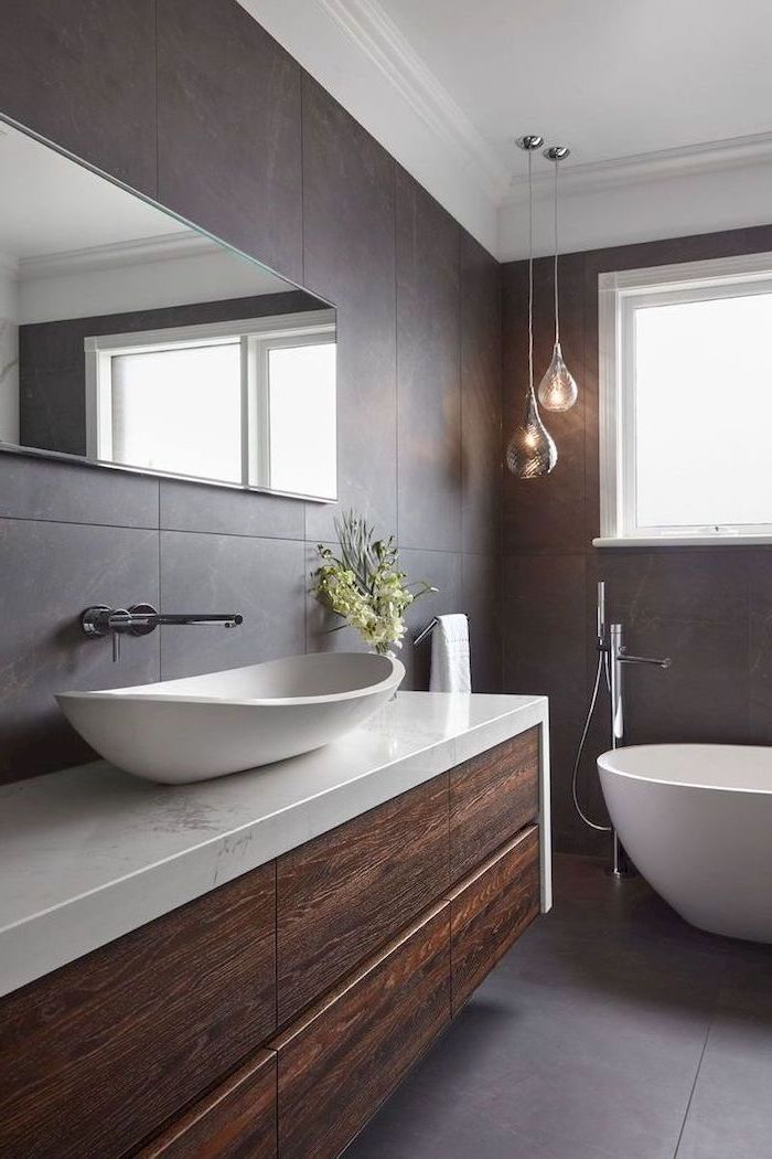 small bathroom remodel floatin wooden cabinet with marble countertop dark tiles on the walls and floor white bathtub