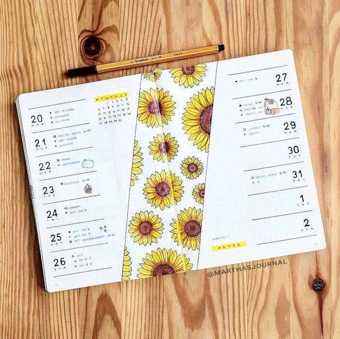 sunflowers drawn on white notebook with separate lines for each day of the month bullet journal ideas placed on wooden surface