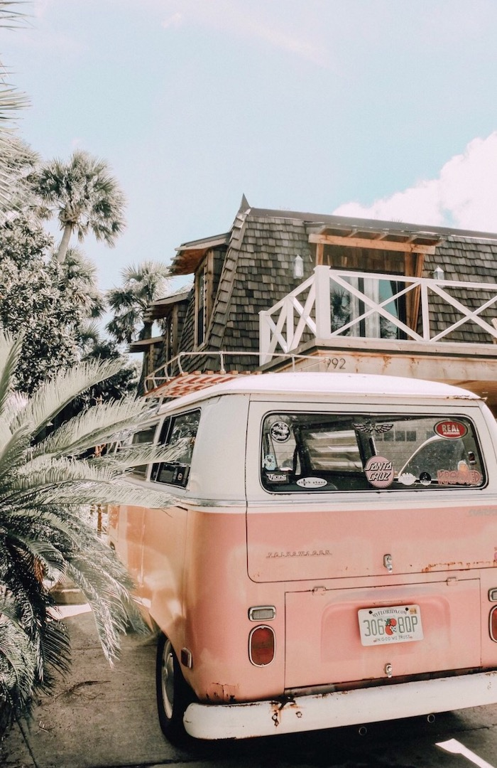 vsco girl backgrounds pink caravan parked in front of house with lots of palm trees in the front yard blue sky above it