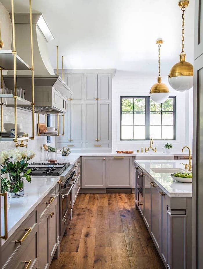 white farmhouse kitchen dark wooden floor light gray cabinets open shelving with brass fixtures white subway tiles backsplash
