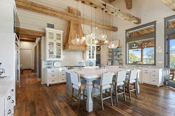white kitchen island with white leather stools rustic farmhouse kitchen exposed wood beams on cathedral ceiling dark wooden floor