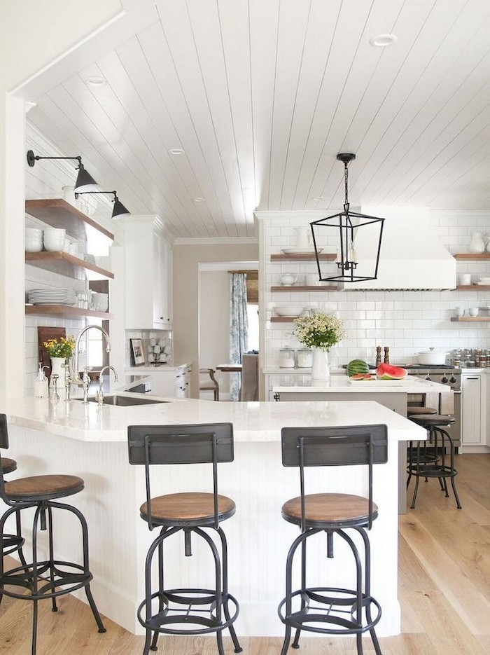 white wooden ceiling white tiles on the walls farmhouse kitchen decor white countertops and cabinets black metal chairs