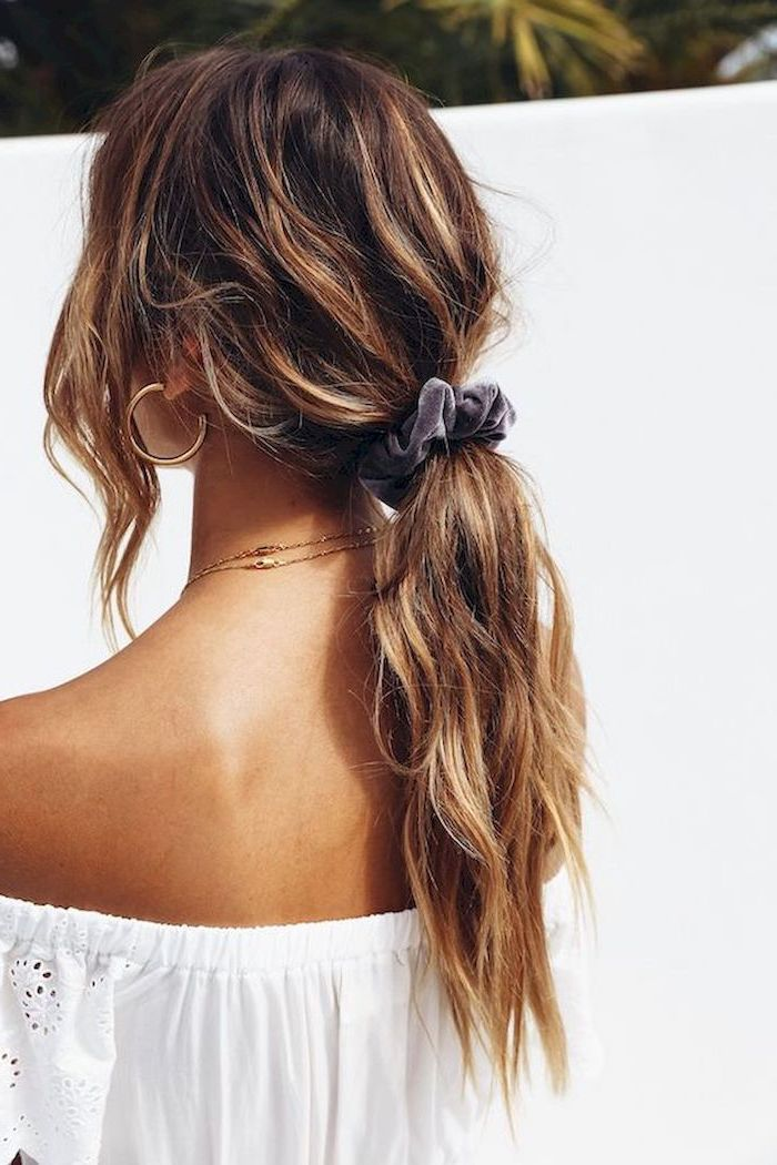 woman wearing strapless white top easy hairstyles for long hair brunette wavy hair with blonde highlights in low ponytail tied with velvet scrunchie