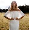 woman with long blonde wavy hair wearing white dress with long train made of lace beaded wedding dresses