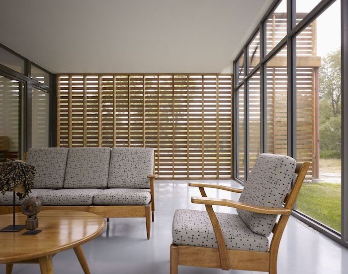 wooden blinds and tall windows screened in patio wooden living room furniture with light gray cushions
