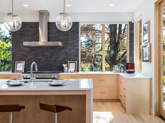 wooden cabinets and kitchen island with white countertops big windows kitchen backsplash ideas black stone tiled backsplash