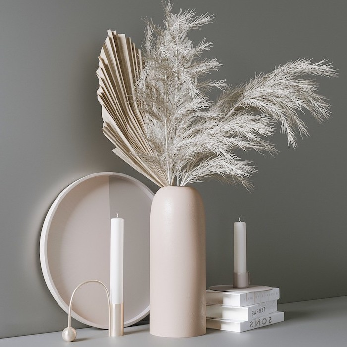 arrangement with white faux pampas grass two candles placed on top of three books with white covers gray wall
