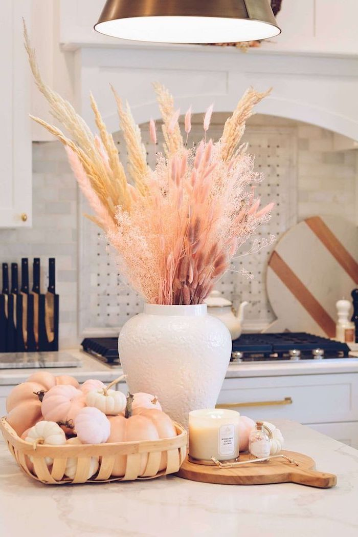 artificial pampas grass inside white ceramic vase placed on top of kitchen island wooden basket with small pumpkins inside