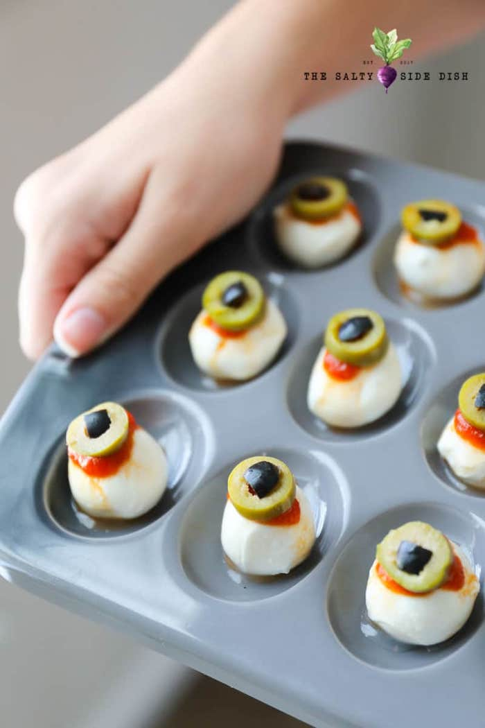 baby mozzarella with salsa and olives arranged in gray muffin baking tray halloween party treats
