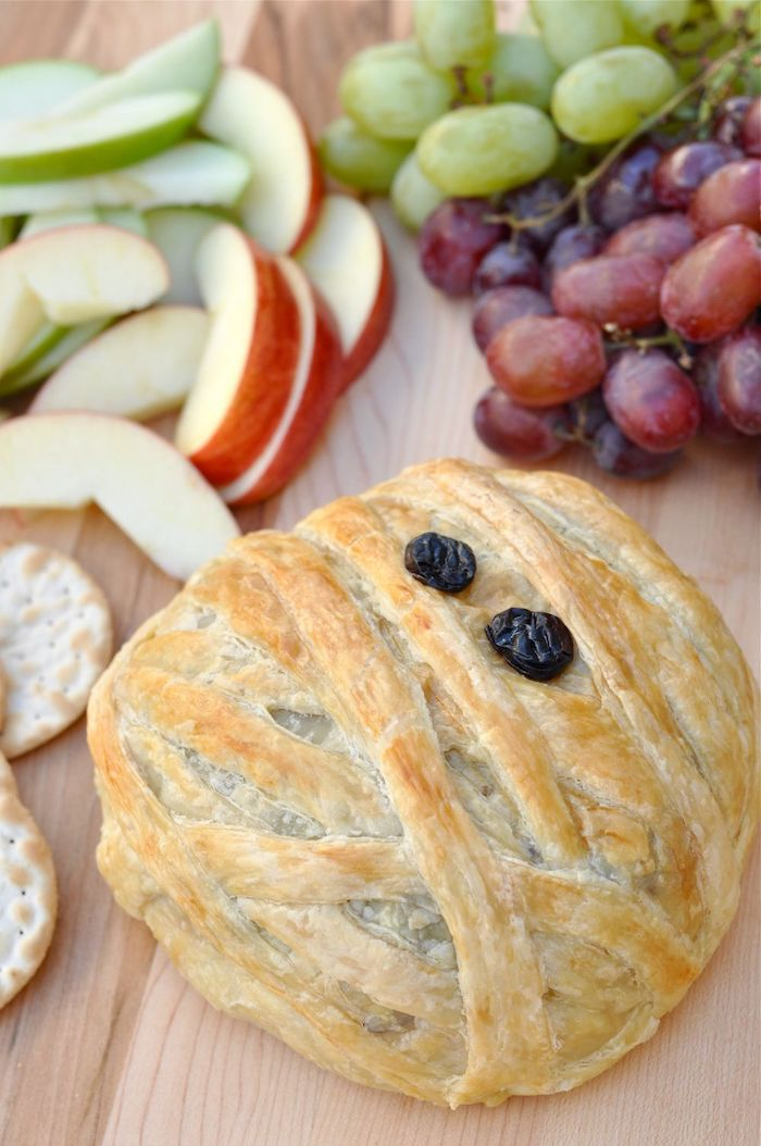 baked brie inside dough as mummy with raisins for eyes halloween finger foods placed on wooden surface