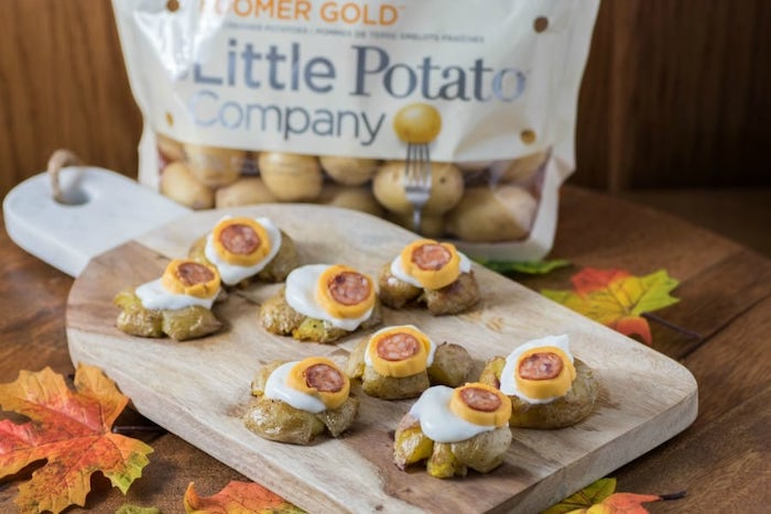 baked potatoes made as monster eye balls with cheese and sausage halloween appetizer ideas arranged on wooden cutting board
