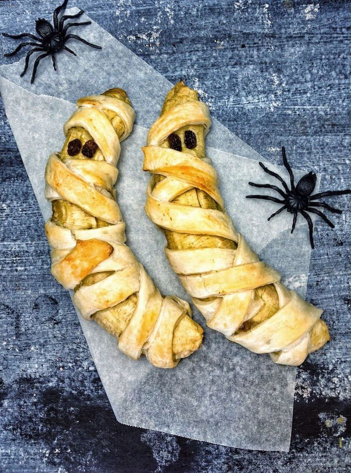 bananas wrapped in dough as mummies placed on baking paper halloween themed food two plastic spiders on the sides
