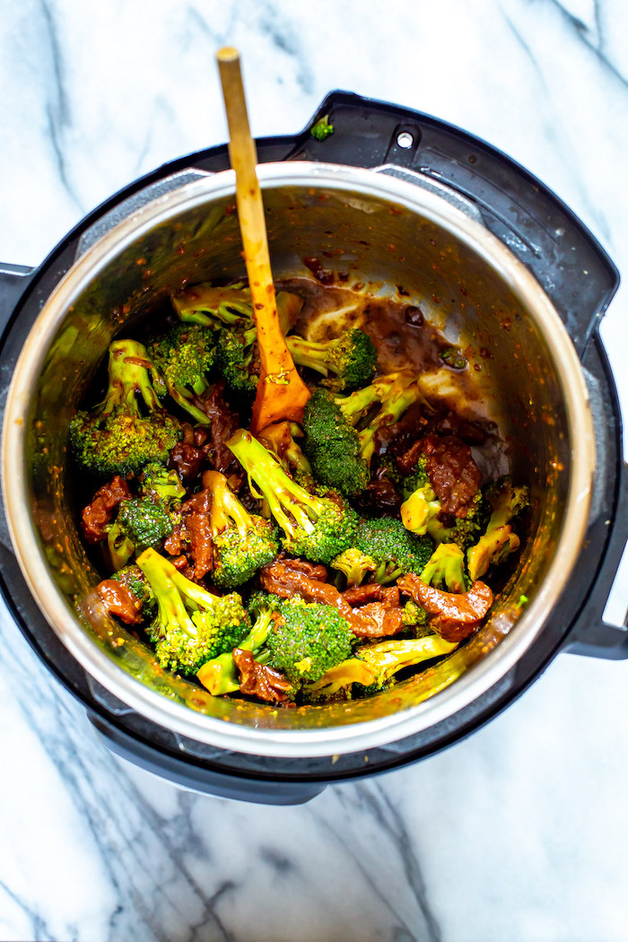 beef and broccoli cooked in instant pot best instapot recipes stirred with wooden spoon placed on marble surface