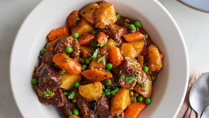 beef stew cooked in instant pot with potatoes carrots peas garnished with chopped parsley instant pot dinner recipes