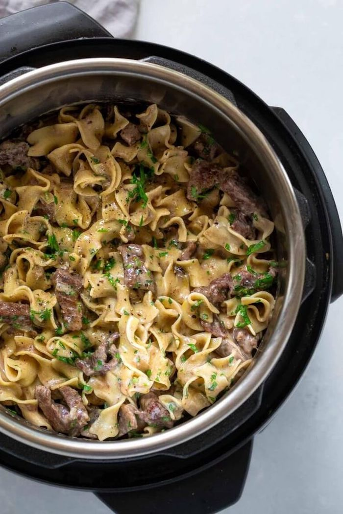 beef stroganoff cooked in instant pot placed on white surface best instapot recipes garnished with chopped parsley