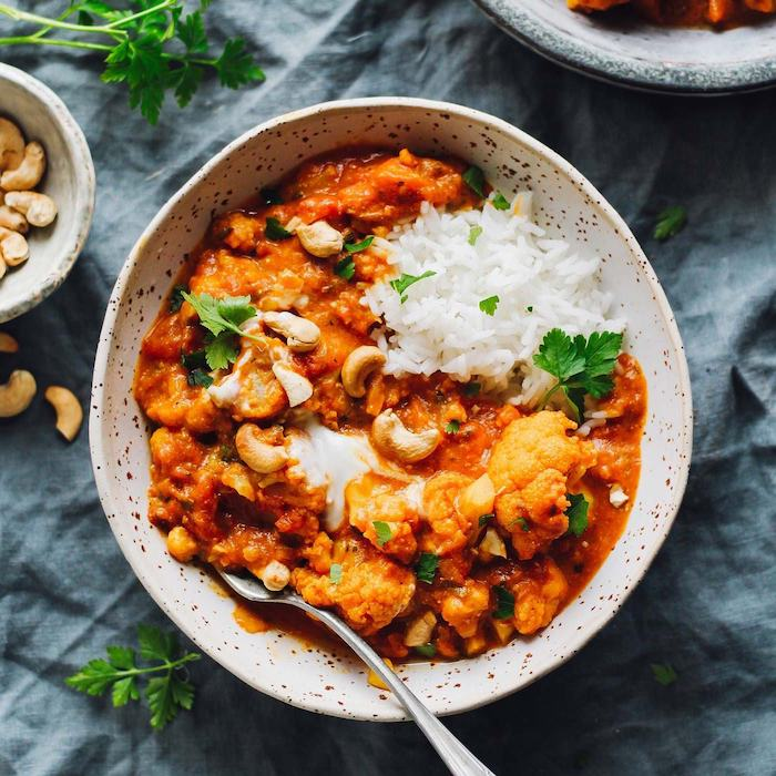 best instant pot recipes cauliflower tikka masala curry with white rice garnished with parsley inside white ceramic bowl