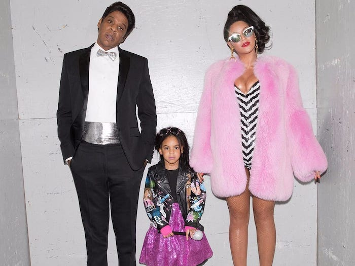 beyonce and jay z dressed as blue ivys barbie and ken family halloween costume ideas standing in front of white wall