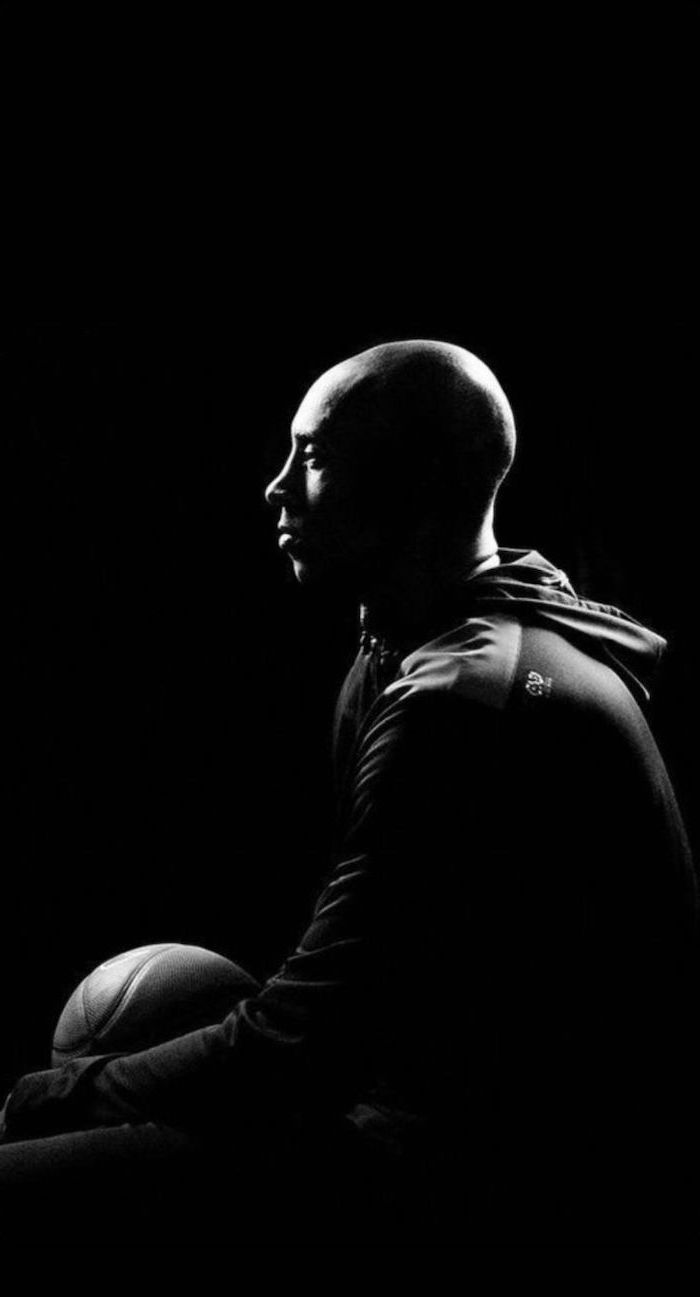 black and white photo of kobe sitting holding a basketball photographed from the side kobe wallpaper black background