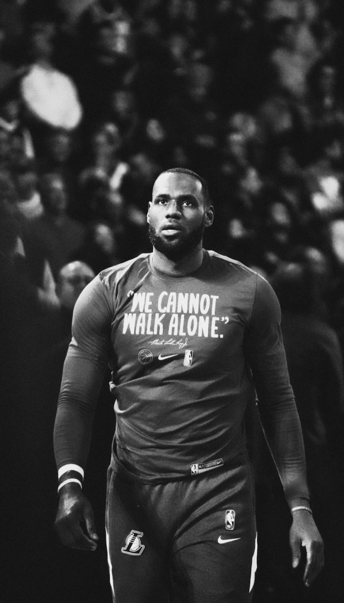black and white photo of lebron walking on the court in warm up clothes best basketball wallpapers we cannot walk alone written on shirt