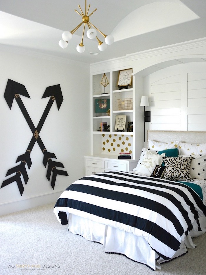 black arrows on white wall cozy teenage girl room bookshelves next to double bed with black white gold throw pillows