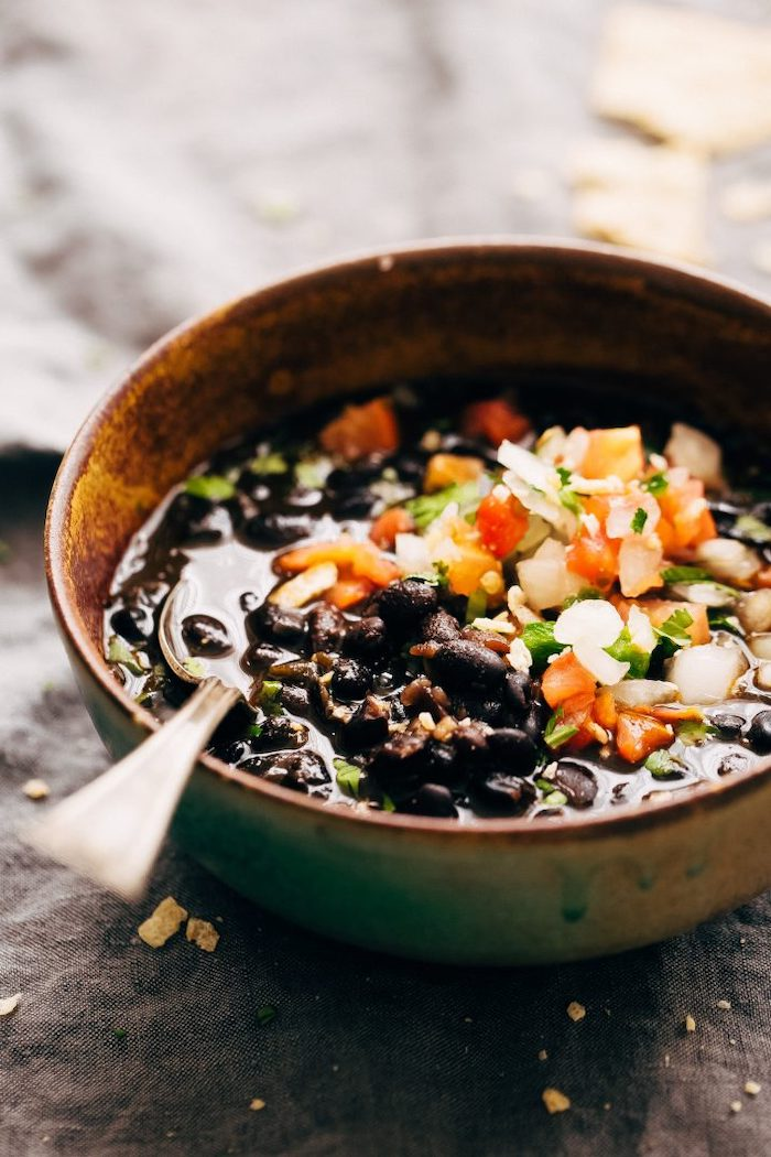 black bean soup inside brown ceramic bowl instant pot one pot meals garnished with parsley chopped tomatoes and peppers