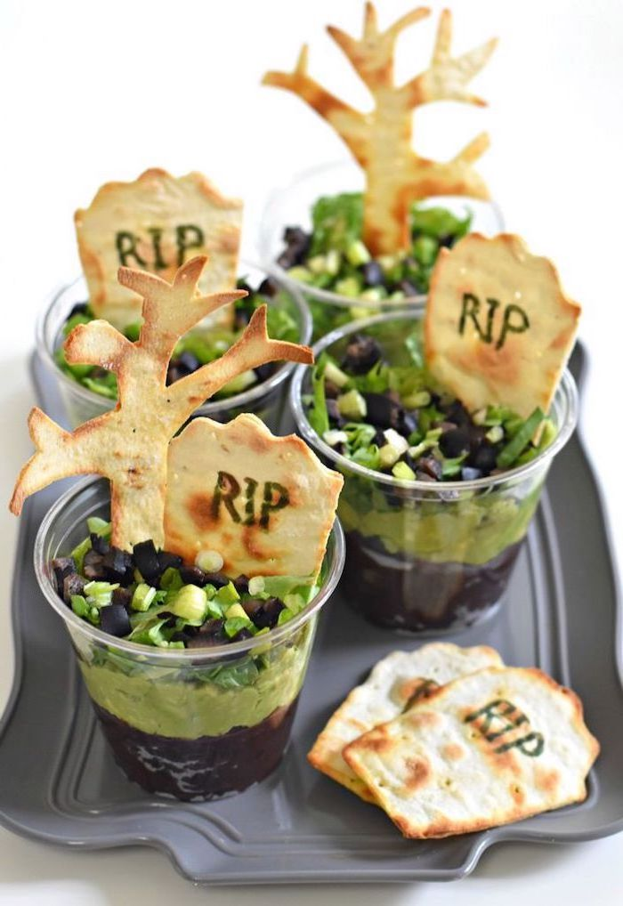black beans and guacamole dip garnished with chives chopped olives inside small cups halloween themed food crackers with rip written on them