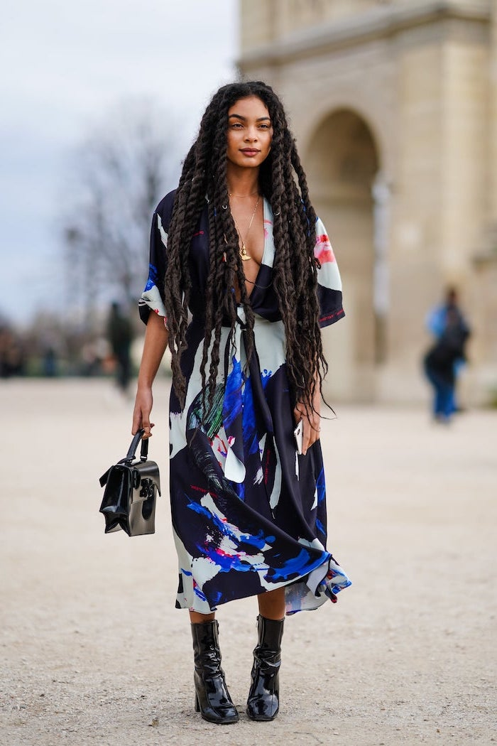 black boots and bag midi dress with abstract colorful rint worn by woman with long black dreads cute trendy outfits standing on the sidewalk