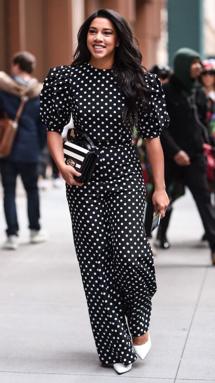 black onesie with white dots statement sleeves white shoes worn by woman with long black wavy hari outfit ideas for women walking down the street