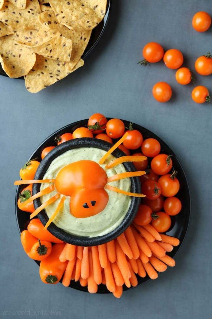 black plate with cherry tomatoes baby carrots orange peppers arranged around bowl of guacamole dip halloween snack ideas placed on gray surface