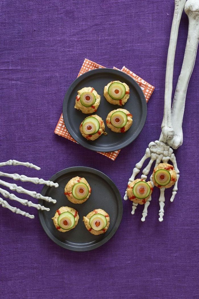 black plates with monster eye bites inside placed on purple table cloth halloween appetizers skeleton hands on the table