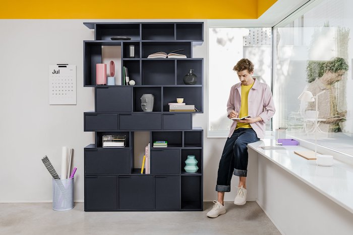 black wooden bookcase with shelves and drawers in different shapes bookcase ideas man standing next to it reading a book